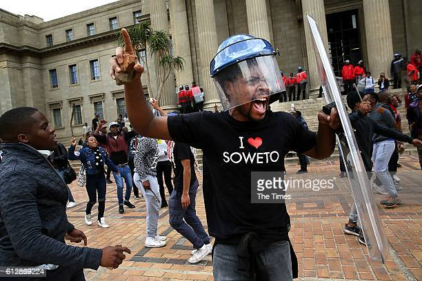 A Wits University student leader Mcebo Dlamini wearing what appears to be a security guards helmet and holding a shield confronts police with a rock...