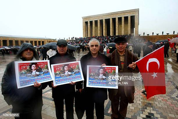 Wives and relatives of retired and active military officers charged in the socalled Sledgehammer trial hold a national flag and banners featuring...