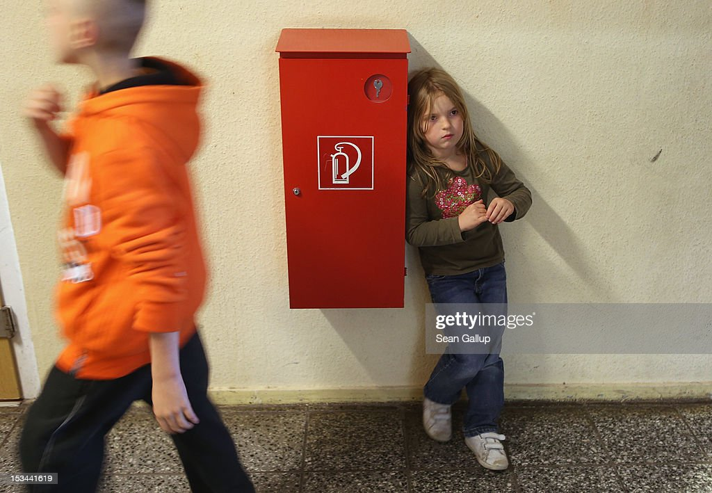 Wiwi (pronounced Vivi), 7, stands in a hallway at the 'Arche' youth center in Marzahn-Hellersdorf district on October 5, 2012 in Berlin, Germany. The Arche (which means Ark) is a Christian-based facility that provides children of all ages with a hot lunch, help with homework, arts and play facilities and in general a welcome place to come to in Marzahn-Hellersdorf district in east Berlin, a district with high levels of unemployment and social problems. An employee said up to 90% of the children come from challenged families and that many arrive at Arche illiterate.