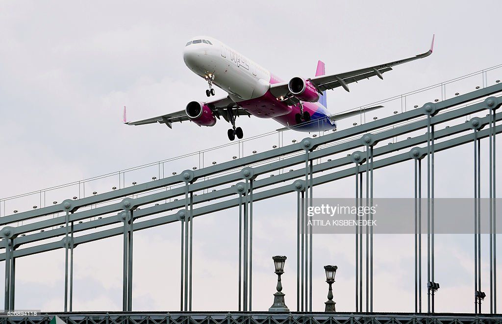 A Wizz Air Airbus A321 flies over the oldest Hungarian bridge, the 'Lanchid' (Chain Bridge) of Danube River in Budapest on May 1, 2016 during the Budapest Air Show. / AFP / ATTILA
