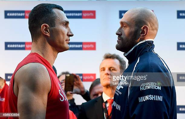 Wladimir Klitschko of Ukraine and Tyson Fury of UK are seen during the weigh in at Karstadt Sport on November 27 2015 in Essen Germany