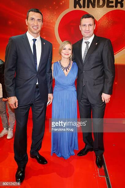 Wladimir Klitschko Regina Halmich and Vitali Klitschko attend the Ein Herz Fuer Kinder Gala 2015 show at Tempelhof Airport on December 5 2015 in...