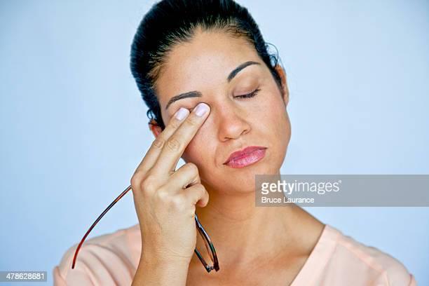 Wman rubbing her eye