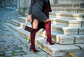 Woman in high heel boots holding bag and coat
