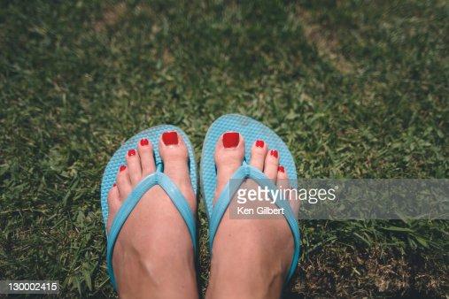 Wman's pedicured feet in flipflops rest on grass