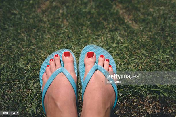 Wman's pedicured feet in flipflops rest on grass