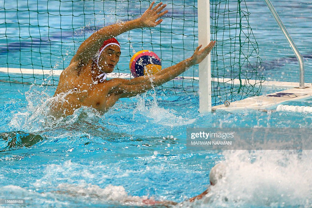 Wo Ka Chan (L) goalkeeper of Hong Kong fails to block a shot by Li Bin of China during their quarterfinal water polo game at the 9th Asian Swimming Championships in Dubai, on November 23 2012. AFP PHOTO/MARWAN NAAMANI