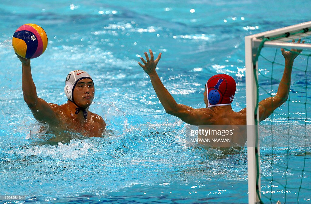 Wo Ka Chan (R) goalkeeper of Hong Kong tries to block a shot by Jian Zhang of China during their quarterfinal water polo game at the 9th Asian Swimming Championships in Dubai, on November 23 2012.