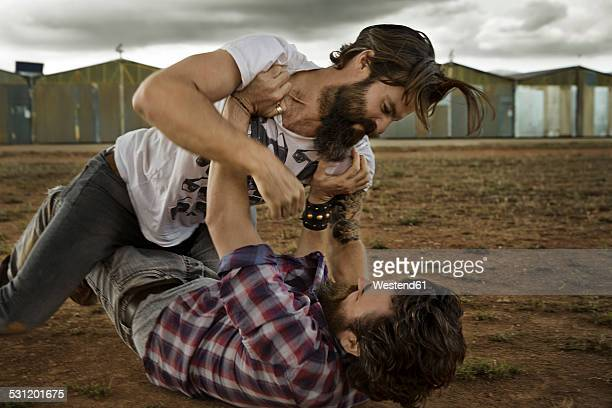 wo men with full beards fighting in abandoned landscape