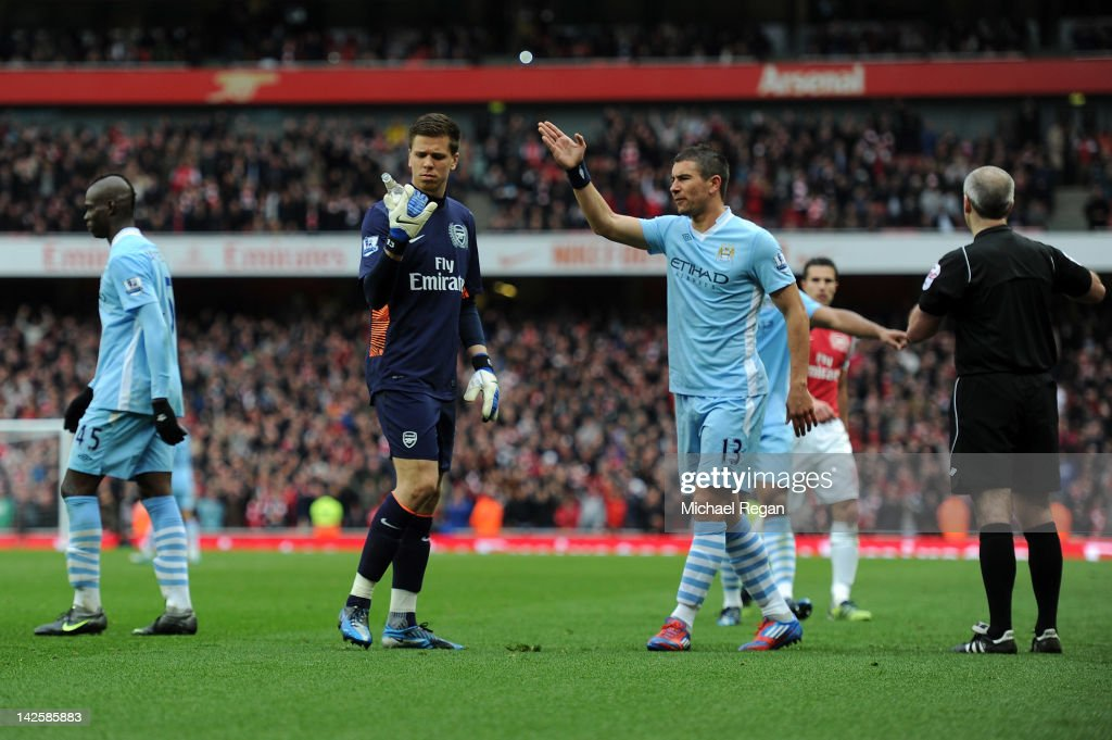 Wojciech Szczesny of Arsenal looks at a bottle of beer that was thrown onto the pitch during the Barclays Premier League match between Arsenal and Manchester City at Emirates Stadium on April 8, 2012 in London, England.