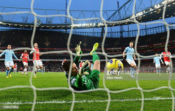 Wojciech Szczesny of Arsenal saves a penalty from Edin Dzeko of Manchester City during the Barclays Premier League match between Arsenal and...