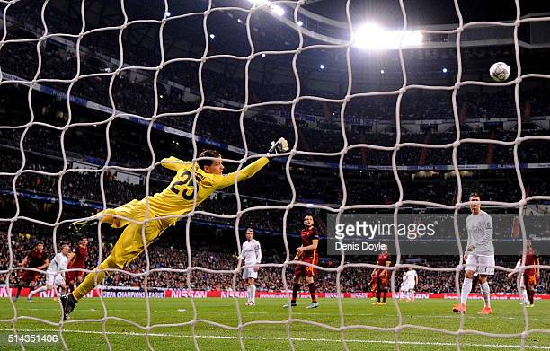 Wojciech Szczesny of AS Roma dives to save a shot on goal during the UEFA Champions League Round of 16 Second Leg match between Real Madrid CF and AS...