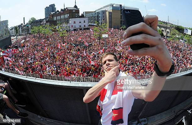 Wojciech Szczesny takes a photo at the Arsenal Victory Parade after winning the FA Cup Final on May 18 2014 in London England