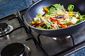 Stir fry vegetables in a wok, on a stove, cooking asian dish