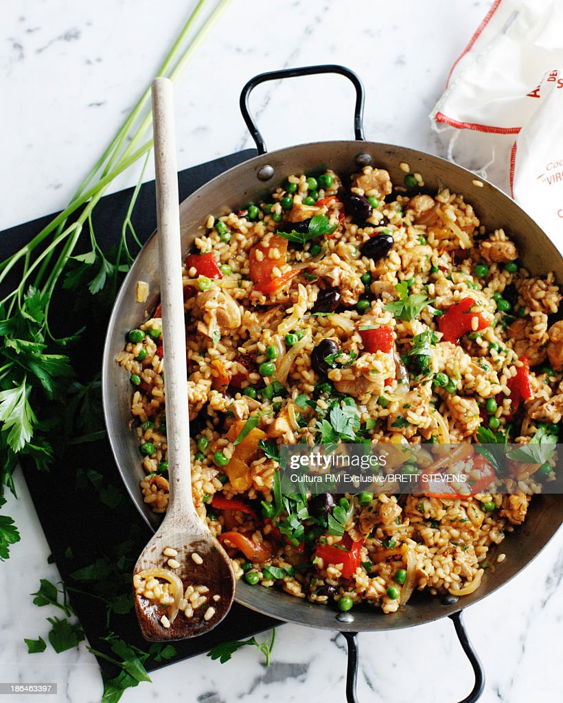 Wok with chicken paella with vegetables and parsley