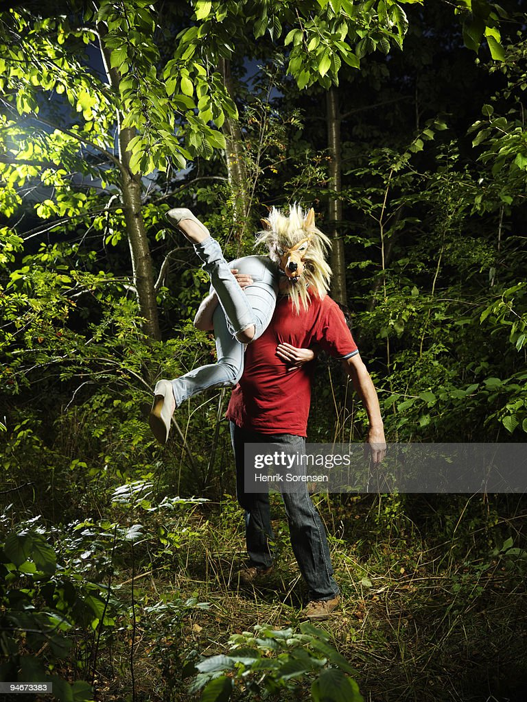 Wolf man with female victim over shoulder : Stock Photo