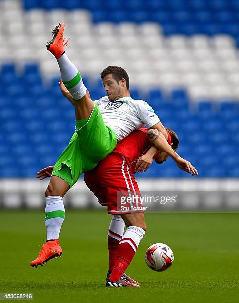 Wolfburg player Vieirinha is challenged by Cardiff player Guido Burgstaller during the friendly match between Cardiff City and VFL Wolfsburg at...