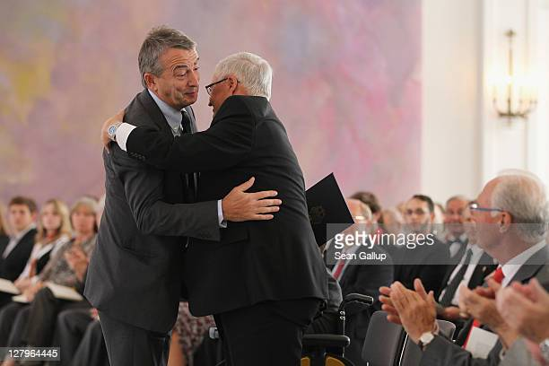 Wolfgang Niersbach General Secretary of the German Football Federation gets a hug from DFB President Theo Zwanziger as Franz Beckenbauer looks on...