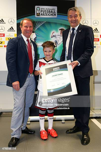 Wolfgang Niersbach President of the German Football Association and Berti Vogts hands over a certificate to Julian prior to the international...