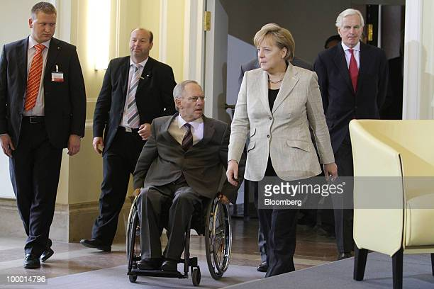 Wolfgang Schaeuble Germany's federal finance minister center left arrives with Angela Merkel Germany's chancellor center right followed by Michael...