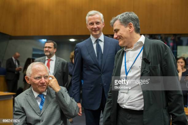 Wolfgang Schaeuble Germany's finance minister left speaks with Euclid Tsakalotos Greece's finance minister right as Bruno Le Maire France's finance...