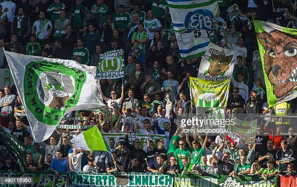 Wolfsburg supporters cheer their team during the German first division Bundesliga football match VfL Wolfsburg vs Hannover 96 in Wolfsburg northern...