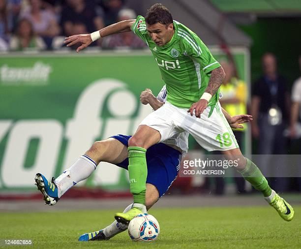 Wolfsburg's Croatian striker Mario Mandzukic vies for the ball with Schalke's Greek defender Kyriakos Papadopoulos during the German first division...