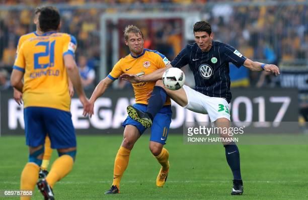 Wolfsburg's forward Mario Gomez and Braunschweig's midfielder Jan Hochscheidt vie during German Bundesliga relegation second leg football match...