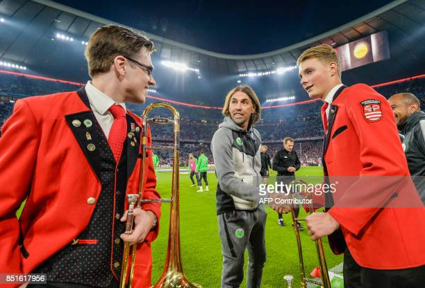 Wolfsburgs head coach Martin Schmidt shakes hands with members of a brass band prior to the German First division Bundesliga football match FC Bayern...
