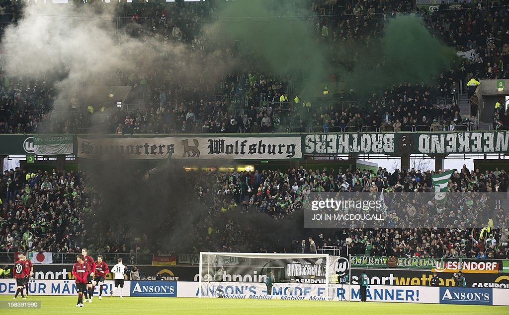 Wolfsburg's supporters light fireworks during the German first division Bundesliga football match Wolfsburg vs Eintracht Frankfurt on December 15, 2012 in Wolfsburg, northern Germany. AFP PHOTO / JOHN MacDOUGALL AT + 49 69 650050