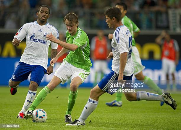Wolfsburg's Swedish striker Rasmus Joensson vies for the ball with Schalke's Peruvian striker Jefferson Farfan and Schalke's Dutch striker KlaasJan...