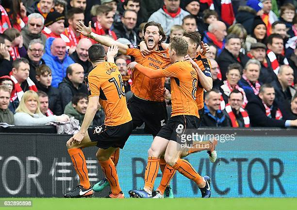Wolverhampton Wanderers' English defender Richard Stearman celebrates with teammates after scoring their first goal during the English FA Cup fourth...