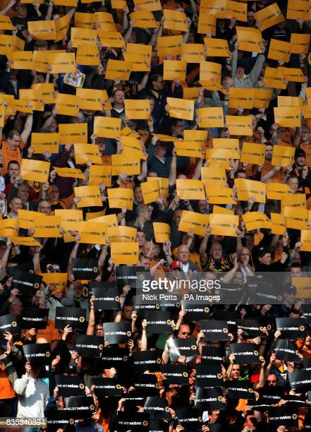Wolverhampton Wanderers' fans holds Gold and Black cards before the CocaCola Championship match at Molineux Stadium Wolverhampton
