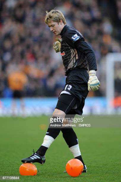 Wolverhampton Wanderers goalkeeper Wayne Hennessey pops a balloon on the pitch