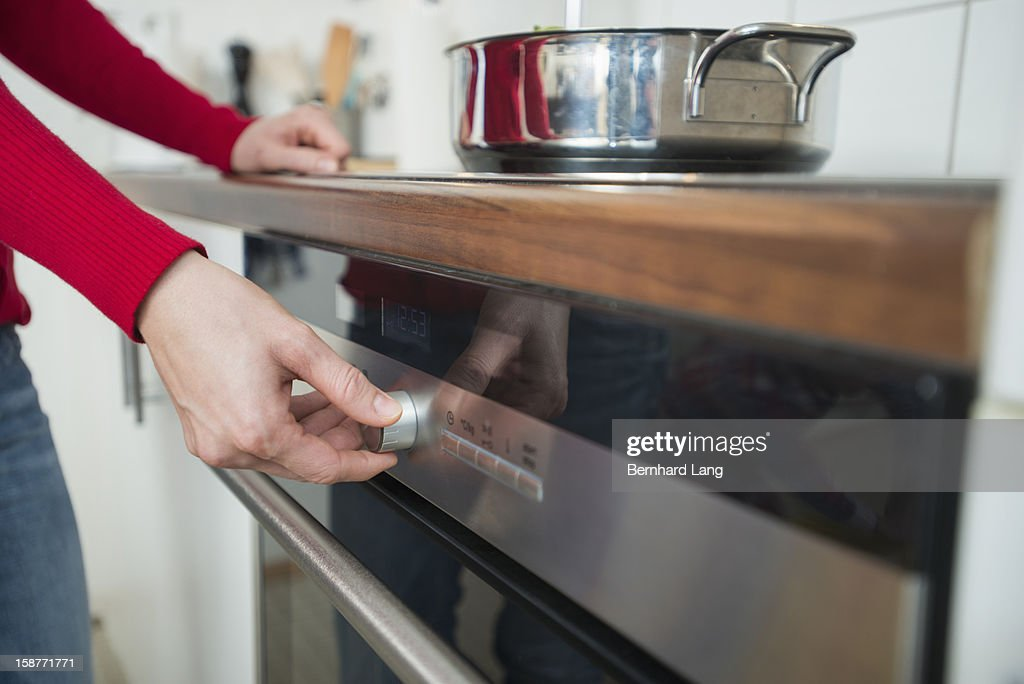 Womam switching on cooker, close up : Stock Photo