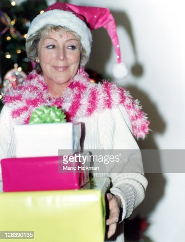 Woman, 60 years old, in pink hat with gifts : Stock Photo
