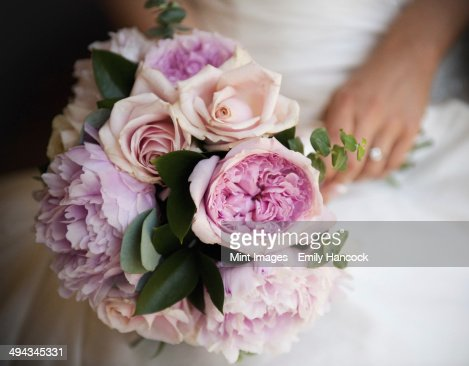 A woman, a bride holding a bridal bouquet of pastel coloured pale pink roses and peonies.