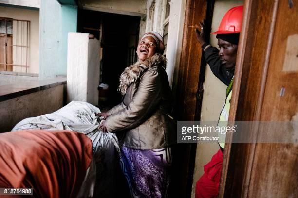 TOPSHOT A woman a Zimbabwean national reacts as a member of the Red Ants a municipal team tasked with evictions supervises her eviction from an...