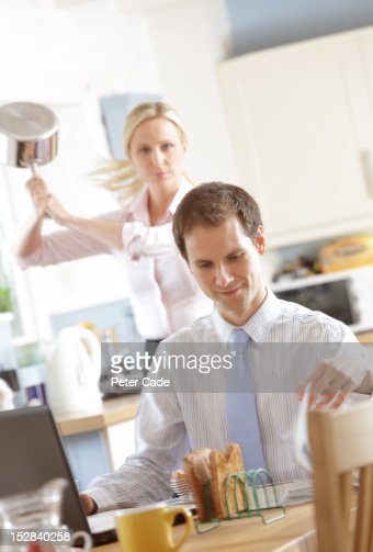 Woman about to hit man with saucepan at breakfast : Stock Photo