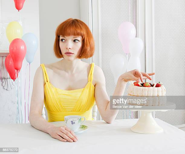 woman about to nibble on large cake