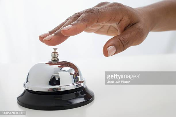 Woman about to ring service bell, close-up of hand