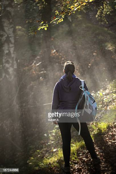 Woman absorbing morning sun in the forest.