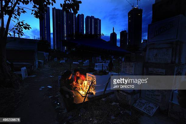 A woman accompanied by her son holds vigil with candles at the tomb of her mother as they honour the dead on All Saint's Day in Manila on November 1...