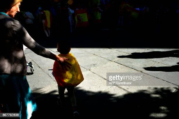 A woman accompanies a boy wrapped with a Spanish flag during a prounity and prodialogue demonstration outside the town hall in Sevilla on October 29...