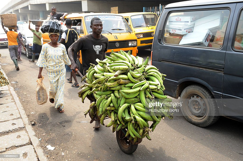 A woman accompanies a man carrying her plantain bananas to a car park at Mile 12 district in Lagos as labour suspend a fiveday strike to dialogue...