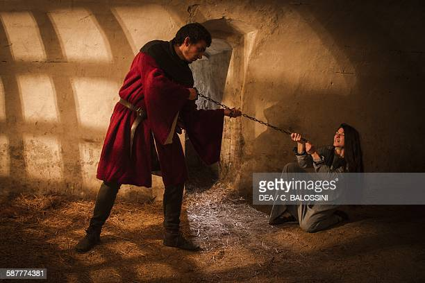 A woman accused of witchcraft held by a chain in a castle cell Northern Italy 15th century Historical reenactment