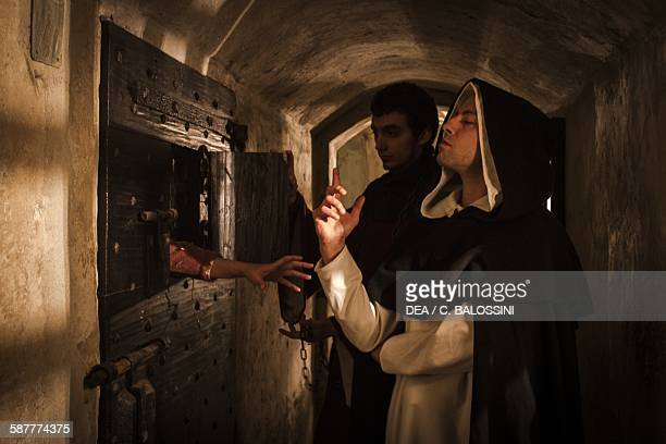 A woman accused of witchcraft in the dungeons of a castle pleading with a monk for comfort Italy Northern 15th century Historical reenactment