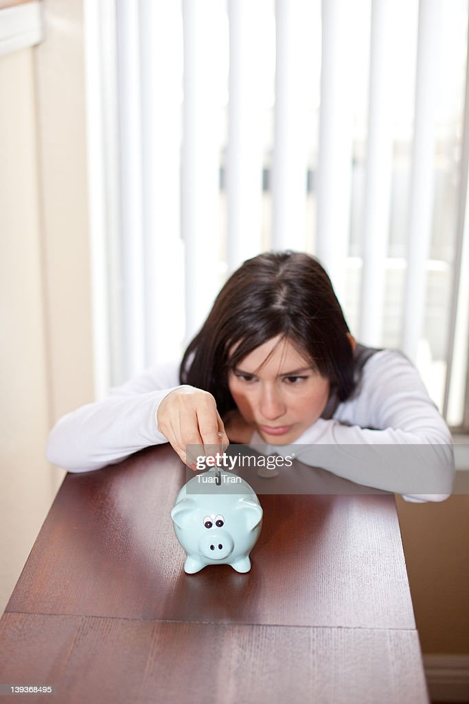 Woman add coin to piggy bank : Stock Photo