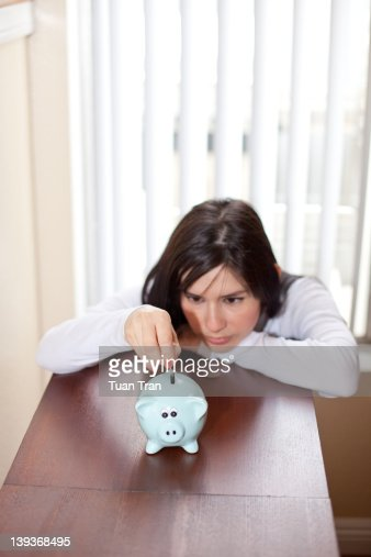 Woman add coin to piggy bank : Stockfoto