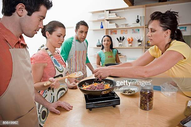 Woman adding ground beef into skillet